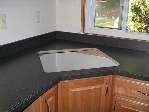 The corner of the countertop, with the sink hole cut and backsplash ...